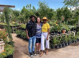 Tonya with arms around two of her children. They are facing the camera and standing among a variety of plants.